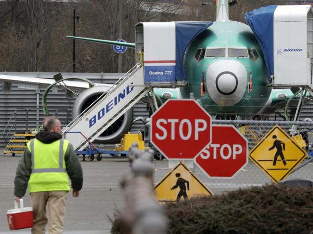 A Boeing worker walks near a 737 Max jet on Monday in Renton, Wash. Boeing said it will suspend production of the troubled jetliner in January.
