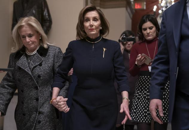 House Speaker Nancy Pelosi (D-Calif.) holds hands with Rep. Debbie Dingell (D-Mich.) as they walk to the chamber where the House begins debate on the impeachments charges against President Trump.
