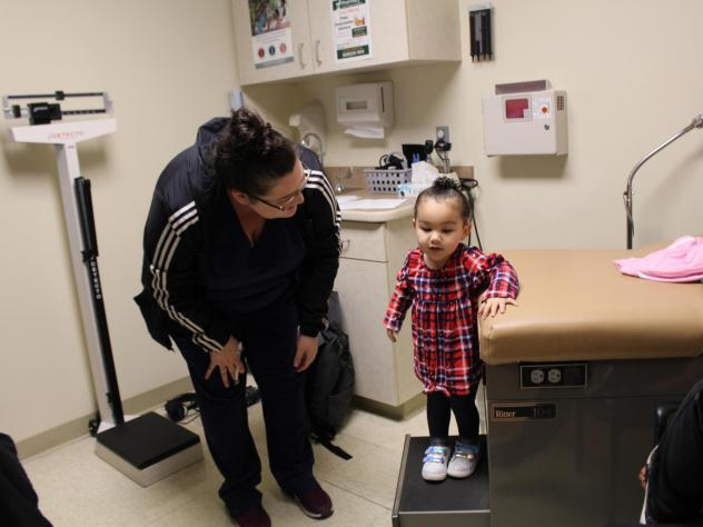 Eliza Oliver helps her daughter, Taelyn, step down from the exam table after a wellness check at the Community Health Center of Southeast Kansas in Fort Scott, Kan. The child's doctor now has a medical scribe to takes notes. The visit this time seemed mo