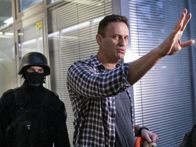 Russian opposition leader Alexei Navalny gestures while speaking to the media as a security officer guards an entrance of the Anti-Corruption Foundation office in Moscow, Russia, Thursday. The federal court bailiffs' service that conducted the Thursday r
