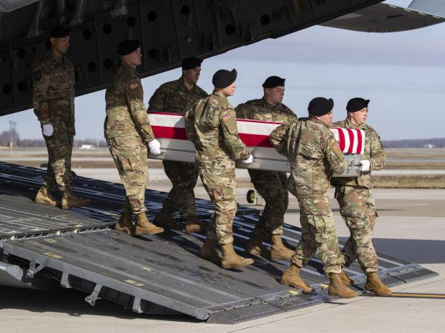 In this Dec. 25 photo, an Army carry team moves a transfer case containing the remains of U.S. Army Sgt. 1st Class Michael Goble, at Dover Air Force Base in Delaware. The U.S. Special Forces soldier died in Afghanistan this week while seizing a Taliban w