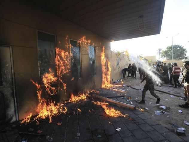 Outraged Iraqi protesters, angered by U.S. strikes on armed battalions belonging to an Iranian-backed militia, attack the U.S. Embassy in Baghdad on Tuesday.