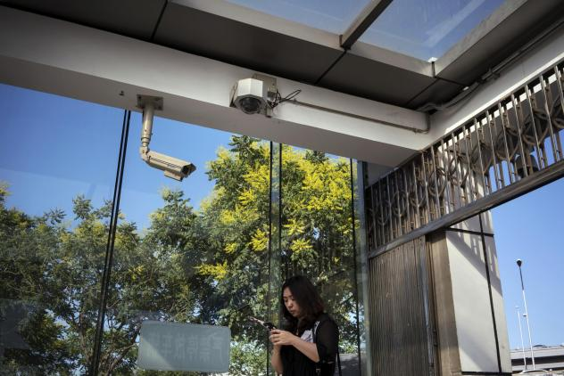 A pedestrian uses a smartphone while standing under surveillance cameras in Beijing last May.