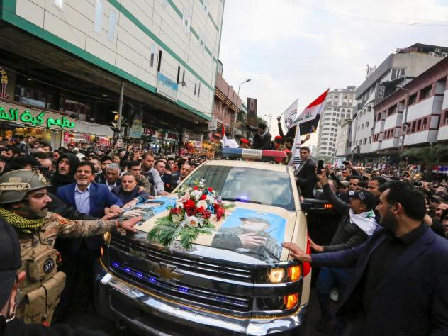 Mourners surround a vehicle carrying the coffins of Iranian Maj. Gen. Qassem Soleimani and Iraqi militia leader Abu Mahdi al-Muhandis, during a funeral procession Saturday in Baghdad.