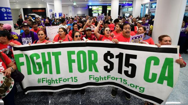 Airport employees, Uber and Lyft drivers, and other workers protest for a $15 minimum wage at Los Angeles International Airport in October. Increases in minimum wages contributed to bigger pay gains for lower-income workers.