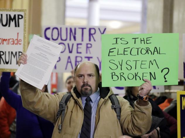 Brock Ervin holds a sign outside the Indiana House chamber at the Statehouse before the 11 representatives of the Electoral College gathered on Dec. 19, 2016, in Indianapolis.  The U.S. Supreme Court has agreed to hear two cases challenging state attempt