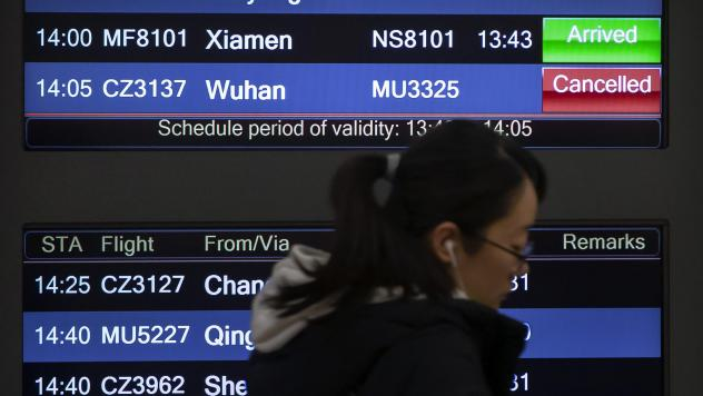 A traveler walks past a display board showing a canceled flight from Wuhan at Beijing Capital International Airport on Thursday. China closed off the city of more than 11 million in an unprecedented effort to try to contain a deadly new viral illness tha