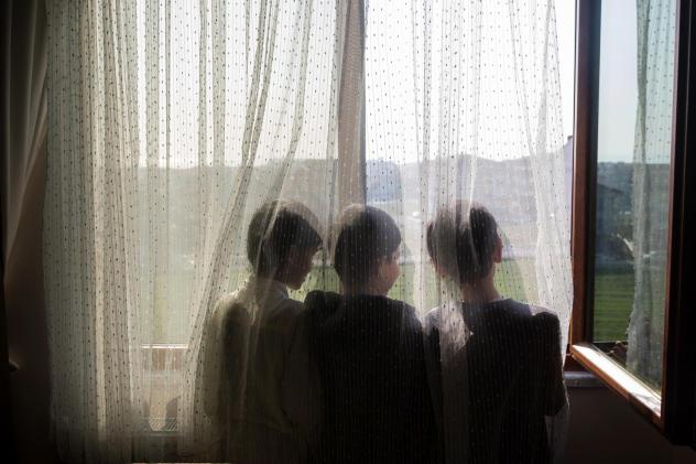 Ten-year-old Nurzat (right) and his friends, brothers Abdulla (left), 11, and Muhammet (center), 10, look out the window of their dormitory room at a boarding school in Istanbul, Turkey. The boys are all missing their parents, who are believed to be in p