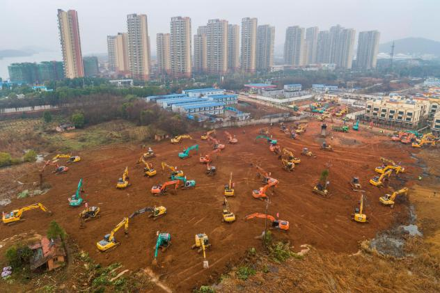 Excavators are seen at the construction site of a medical center being built in Wuhan, China, to treat patients of the coronavirus outbreak. Ground was broken on Jan. 24. The scheduled opening is Feb. 3.