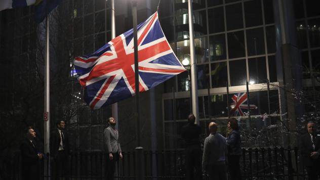 Officials lower and remove the Union Jack from the European Parliament building in Brussels on Friday. As the U.K. prepared to bring to an end its decades-long membership in the European Union, the bloc's top officials on Friday pledged to continue playi