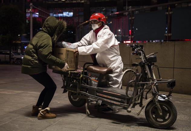 A delivery person wears a protective mask and suit as he delivers packages by bicycle on Saturday in Wuhan, China.