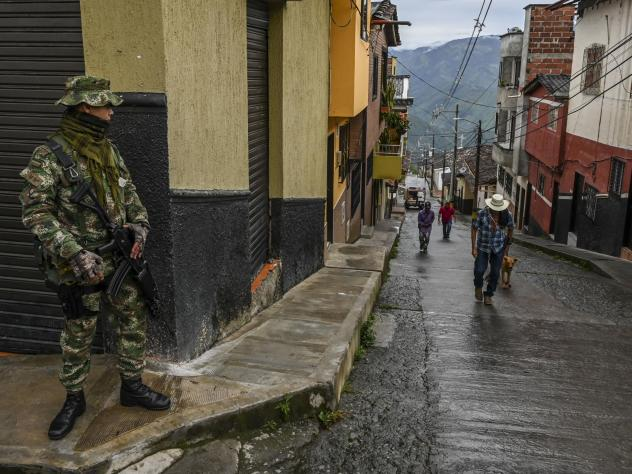 A soldier stands guard on a street in Ituango, Colombia, on Oct. 19, 2019. The town is home to a new public radio station staffed by ex-FARC rebels and war victims. Reporters often conduct interviews with former combatants and update listeners on the pro