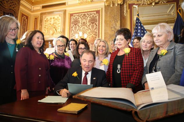 Utah Gov. Gary Herbert signs bill honoring the state's pioneering women suffragists on Wednesday. He's surrounded by state senators and representatives, and his wife, who are all wearing the yellow rose symbolizing suffrage.<em> </em>
