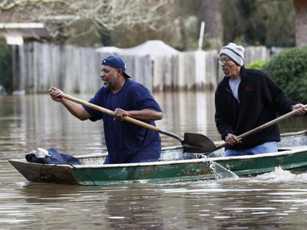 Jackson, Miss., residents use shovels to work their way through Pearl River floodwaters on Sunday.