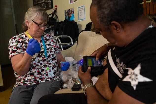 Arthur Jackson (right) gets blood tests during home visits in Boston from nurse Brenda Mastricola. He's also getting intravenous penicillin to treat a serious bone infection in his foot. The medication's pump is connected to an indwelling IV catheter. It