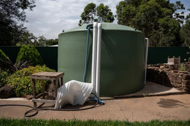 A tank of water sits outside Milbourne's home.