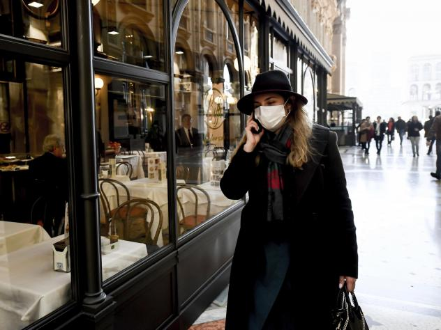 A woman wearing a face mask talks on her phone as she walks in the Galleria Vittorio Emanuele shopping arcade in downtown Milan on Monday. Italy's Health Ministry says the country now has 229 coronavirus cases, with six deaths.