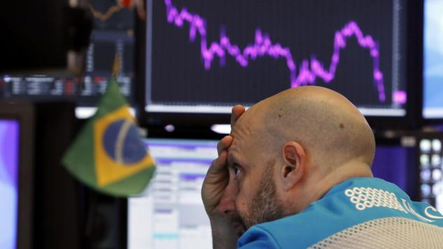 Specialist Meric Greenbaum works at his post on the floor of the New York Stock Exchange on Tuesday. Stocks slumped and bond prices soared for the second day in a row as fears spread that the widening coronavirus outbreak will put the brakes on the globa