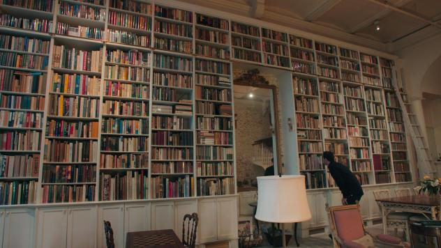 Adam Weinberger examines a bookshelf in the documentary <em>The Booksellers</em>.