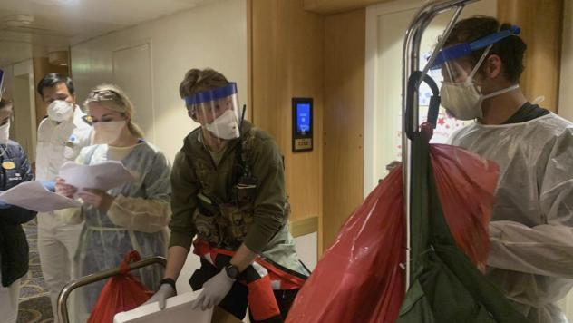 A group of medical personnel with the CDC and the California National Guard 129th Rescue Wing don protective equipment after delivering virus testing kits to the Grand Princess cruise ship off the coast of California.