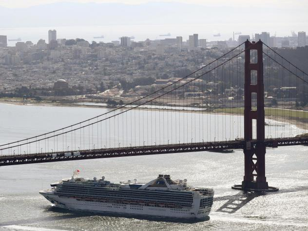 The Grand Princess cruise ship heads under the Golden Gate Bridge to a port in Oakland, Calif., on Monday. The ship's more than 2,400 passengers are headed to either medical care or a quarantine due to the coronavirus.
