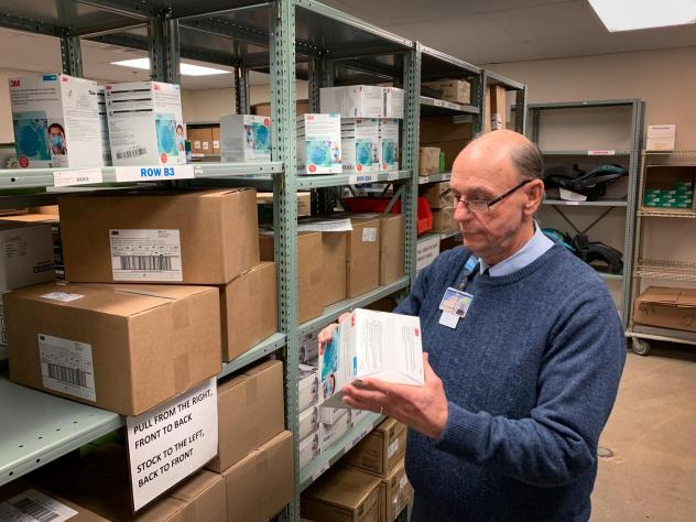 Tom Cooper, Nashville General Hospital's supply chain director, inspects a box of N95 respirators. The hospital is among a small group of pilot sites now sharing data about the inventory of its protective equipment with the Centers for Disease Control an