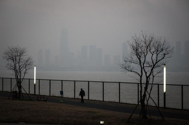 A man walks along the Yangtze River in Wuhan, the city in China where the novel coronavirus was first identified.