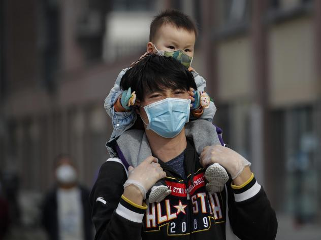A man carries a toddler on his shoulders on a street in Beijing on Wednesday. While China said it had no new domestic coronavirus cases on Thursday, it reported that dozens more had arrived from abroad.