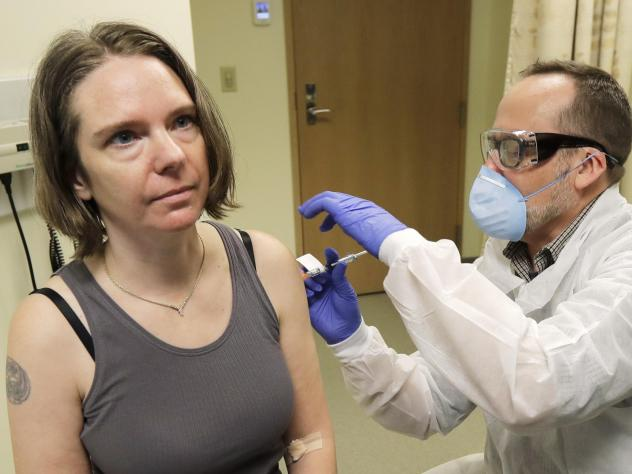 A pharmacist gives Jennifer Haller, left, the first shot in the first-stage study of a potential coronavirus vaccine on March 16, 2020, at the Kaiser Permanente Washington Health Research Institute in Seattle.