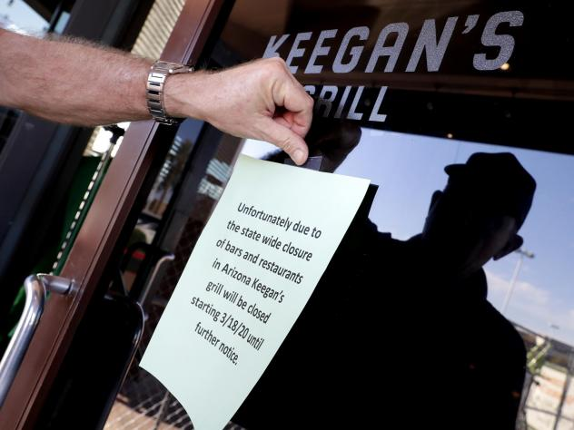 Owner Steve Johnson attaches a notice on the door of Keegan's Grill in Phoenix notifying guests his restaurant will close. Rapid shutdowns have delivered a blow to restaurants around the country.