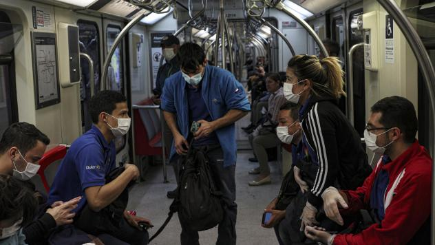 Supermarket workers wear face masks as a precaution against the spread of the new coronavirus inside the metro in Santiago, Chile, on March 18.