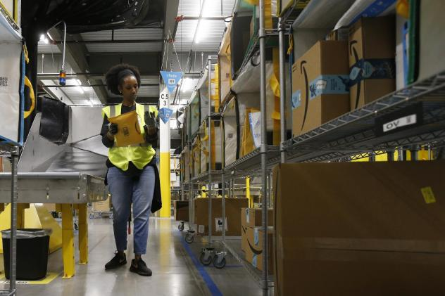 An Amazon worker stows packages into special containers at a facility in Arizona. Coronavirus cases have been reported in at least 7 Amazon facilities.
