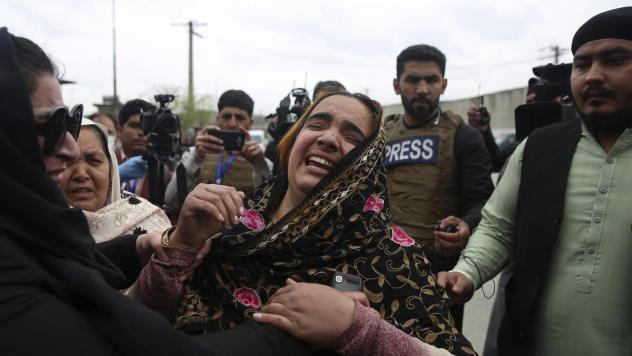 Family members sob for their loved ones after an attack on a Sikh place of worship Wednesday in Kabul, Afghanistan. More than two dozen people were killed in the assault, for which Islamic State militants claimed responsibility.
