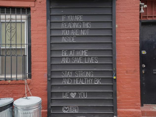 """A message about staying home during the coronavirus pandemic is shown on a gate in the Williamsburg section of Brooklyn. The rate of new coronavirus cases in New York state is """"doubling about every three days,"""" Gov. Andrew Cuomo said Tuesday."""
