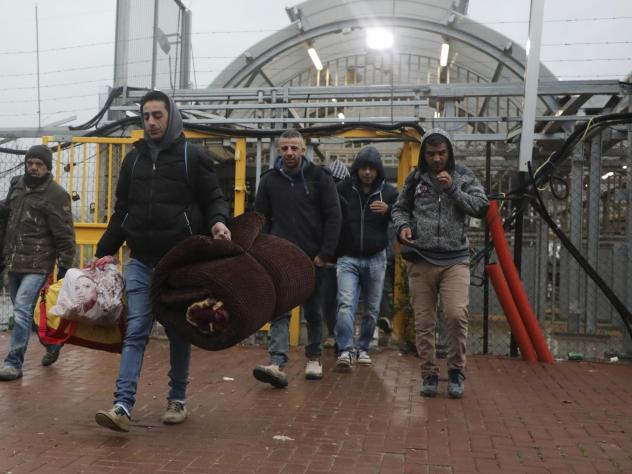 Palestinian laborers enter Israel on March 18 through a checkpoint between the West Bank city of Hebron and Beersheva. They carry blankets and mattresses, in preparation to stay in Israel amid the coronavirus pandemic.
