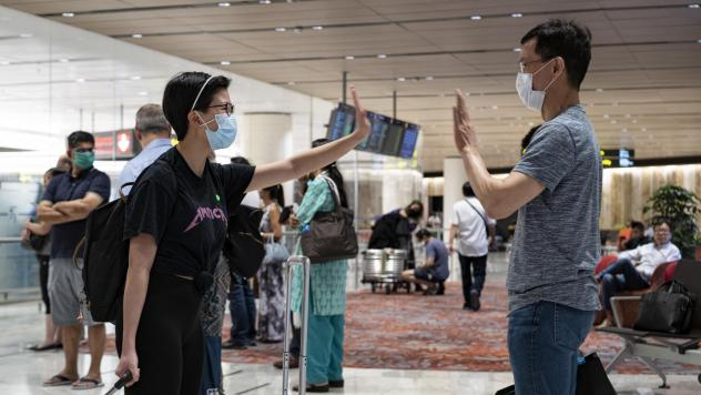 New arrivals greet each other without touching at Changi Airport earlier this week in Singapore. The island country, which imposed a ban on short-term visitors shortly after this photograph was taken, has now also implemented the threat of prison time fo