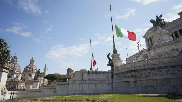 During a minute of silence commemorating COVID-19 victims, flags fly at half-staff Tuesday at Rome's monument to the unknown soldier.
