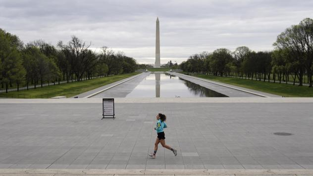 A woman jogs along a mostly empty National Mall on March 31, 2020 in Washington, D.C. To prevent the spread of the coronavirus, Virginia, Maryland and the District of Columbia all announced stay-at-home orders this week, which strongly discourage residen