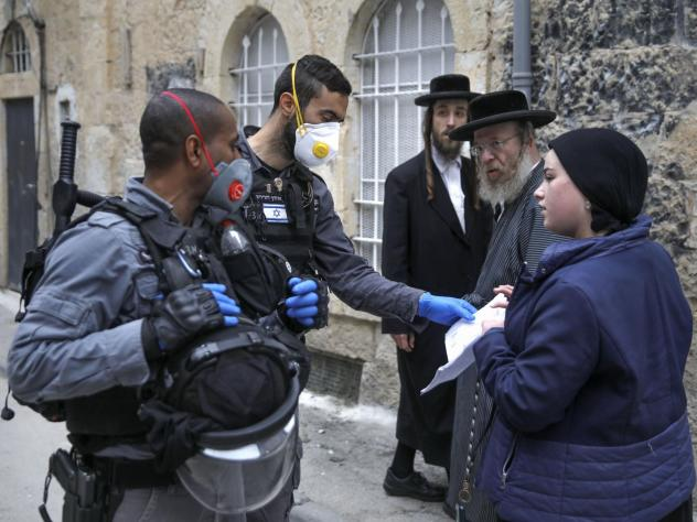 Israeli police officers wearing protective gloves and masks check papers as they enforce restrictions in an ultra-Orthodox Jewish neighborhood in Jerusalem on Tuesday, during a partial lockdown to curb spread of coronavirus infection.
