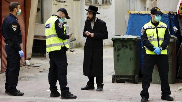 An ultra-Orthodox Jewish man is questioned by an Israeli police officer as part of the government's measures to stop the spread of the coronavirus, in the Orthodox city of Bnei Brak, a suburb of Tel Aviv, Israel, on Tuesday.