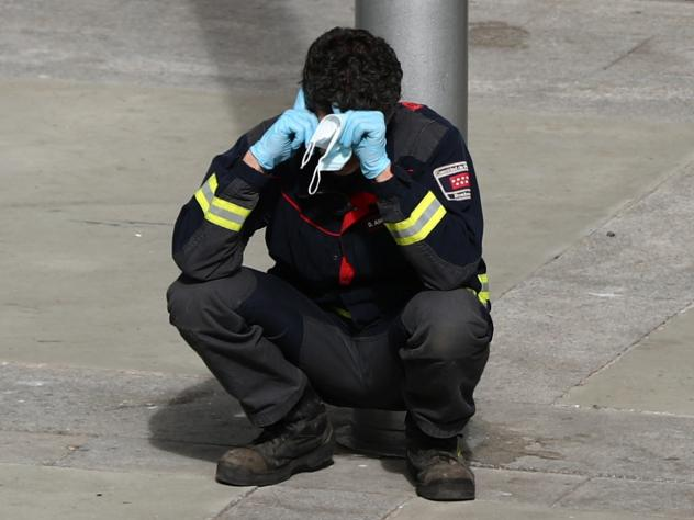 A firefighter takes a moment to rest outside a temporary hospital in a conference center in Madrid, Spain, that was set up as an overflow area for COVID-19 patients. More than a million coronavirus cases are now reported worldwide, putting intense pressu