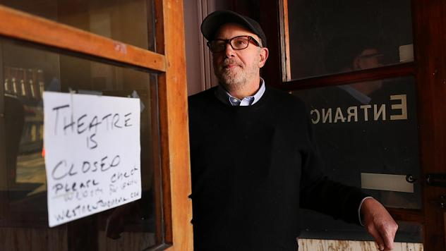 David Bramante, the owner of West Newton Theatre in Newton, Mass., stands in the doorway of the theater noting its closure on March 27.