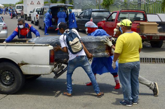 Men load a coffin onto a pickup truck in front of General del Guasmo Sur Hospital in Guayaquil, Ecuador. The port city is the most affected by COVID-19 in the country. Corpses lie in apartments for days and morgues are overcrowded. The city administratio