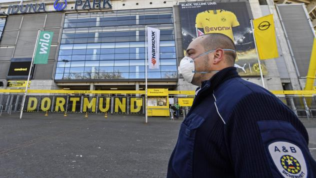 Security with face masks stand in front of the Signal Iduna Park, where a temporary coronavirus treatment center opened in Dortmund, Germany, Saturday. Germany has the fourth-most COVID-19 cases in the world and demand for medical supplies has skyrockete