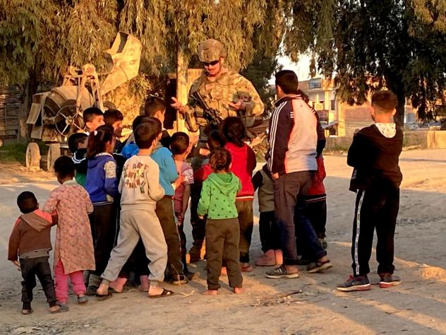 A soldier holds his hands up trying to tell the children he is out of lollipops. Kurdish refugees are streaming in to Tal Tamr and nearby villages in Syria.