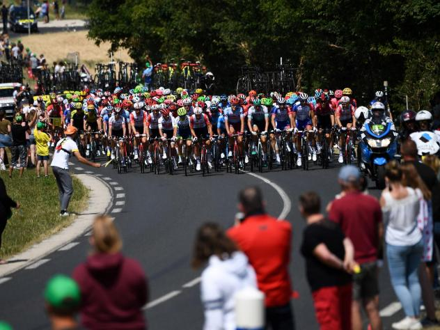Spectators watch cyclists compete in the fourth stage of the Tour de France in eastern France last July. Organizers say the 2020 race will be postponed, though new dates have not been set.