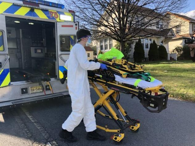Teaneck Volunteer Ambulance Corps member Bobby Alexiou, 20, wheels out a stretcher outside the home of a potential COVID-positive patient in Teaneck, N.J., after suiting up in a protective suit, donated goggles from the local high school and an N95 mask.
