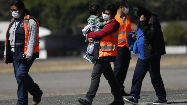 An immigration worker in an orange jacket carries a young Guatemalan deported from the U.S., followed by another deportee, at La Aurora International Airport in Guatemala City on March 12.