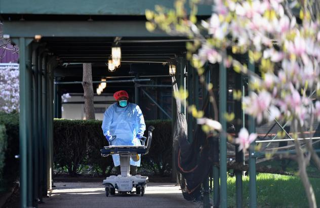 A medical staff member wearing personal protective equipment pushes an empty gurney at Kingsbrook Jewish Medical Center in Brooklyn on April 8. Nurses who gathered in protest outside Kingsbrook earlier this week said a shortage of protective gear at thei