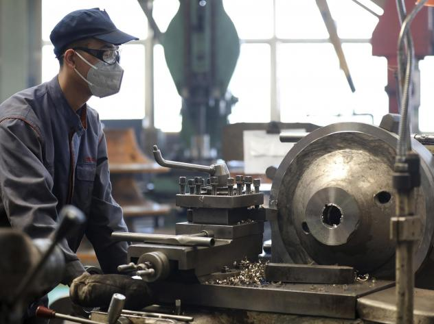 An employee wears a facemask as he works at a blower and fan manufacturing plant in Anshan in northeastern China's Liaoning province, in a photo released by Xinhua on Wednesday.